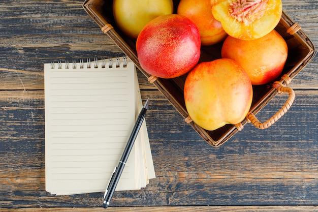 Нектарины с тетрадью, ручка в корзине на деревянном столе, плоское положение.