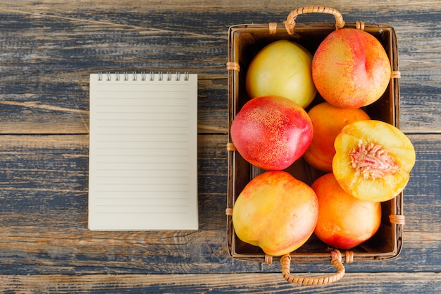 Nectarines with opened notebook in a basket on wooden table, flat lay.