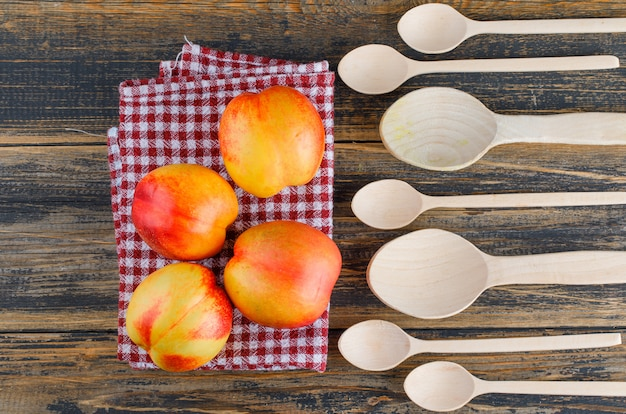 Nectarines with wooden spoons flat lay on wooden and kitchen towel