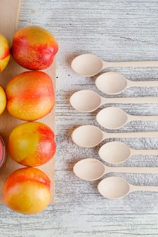 Nectarines with wooden spoons top view on grungy and cutting board table