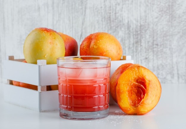 Nectarines in a wooden box with juice side view on white and grungy wall