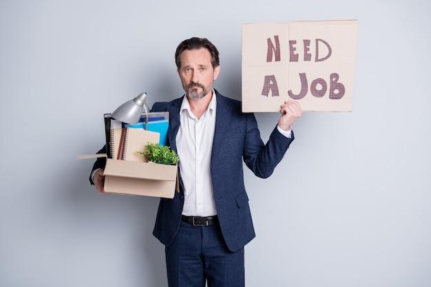 일자리가 필요합니다. 불행한 노동자 성숙한 남자 금융 위기 잃어버린 직장 보류 판지 상자 소지품 해고 정지 현수막 배너 검색 기회 착용 정장 격리 된 회색 배경의 사진