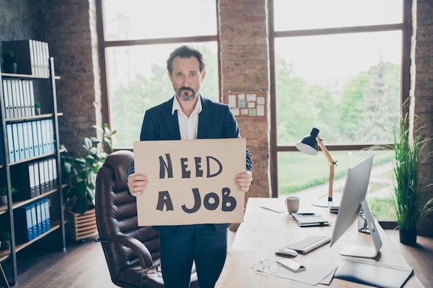 仕事が必要です。不機嫌そうな絶望のプロフィール写真解雇されたサラリーマン成熟した男がプラカードのポスターを持って新しい仕事を探しています