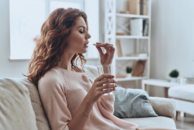 다른 항생제가 필요합니다. 집에서 소파에 앉아있는 동안 약을 복용하는 아픈 젊은 여성