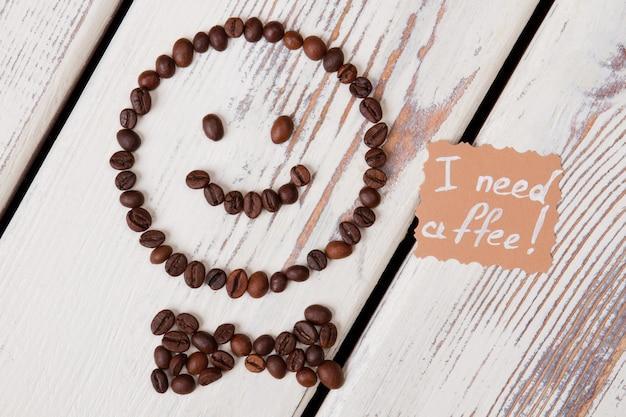커피 개념이 필요합니다. 흰색 나무에 행복 한 웃는 얼굴에 배열하는 커피 콩.