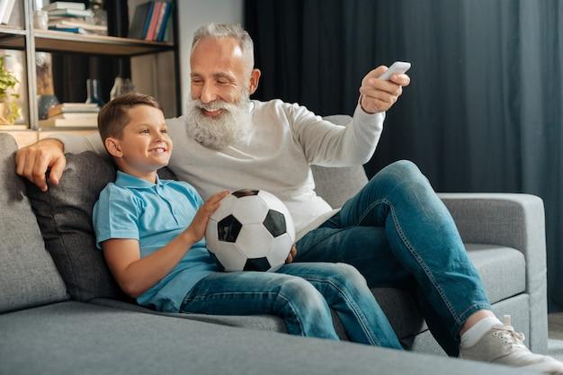 신선한 공기가 필요합니다. 소파에 앉아 공을 들고 그의 손자와 함께 축구 경기를 보는 동안 에어컨을 켜는 즐거운 돌보는 수석 남자