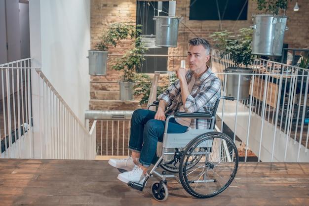 助けが必要。屋内の階段を降りて階段の近くで絶望した車椅子のカジュアルな服を着た悲しい若い大人の男