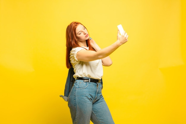 Need minimum clothes for selfie. caucasian woman's portrait on yellow space