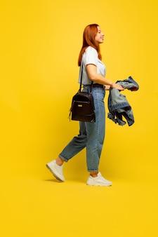 Требуется минимум одежды. портрет кавказской женщины на желтом пространстве