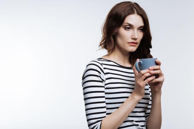 Нужно больше сна. приятная рыжеволосая женщина в полосатом пуловере пьет кофе и выглядит измученной после бессонной ночи.