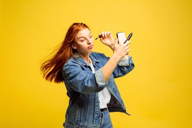 Не нужно селфи для макияжа. портрет кавказской женщины на желтом пространстве