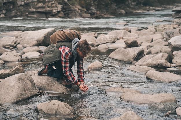 다과가 필요합니다. 산에서 하이킹하는 동안 강에서 물을 마시는 잘 생긴 젊은 현대 남자