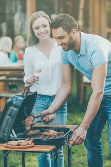 Need some help? happy young couple barbecuing meat on the grill while other members of family sitting at the dining table in the background