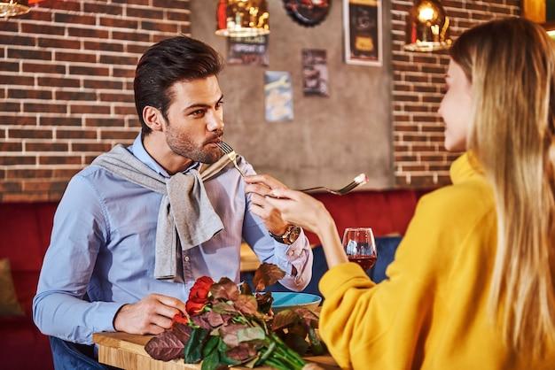 ガールフレンドと食べたり話したりする青いシャツを着た彼女の男を養う必要があります