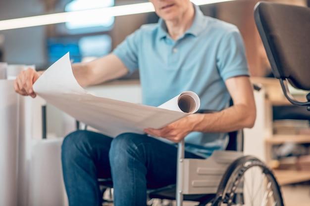 生きる必要があります。屋内の車椅子の人の手に白い紙のロールを広げ、顔が見えない