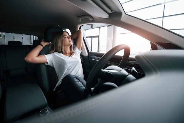 Нужно отдохнуть. девушка в современной машине в салоне. днем в помещении. покупка нового автомобиля.