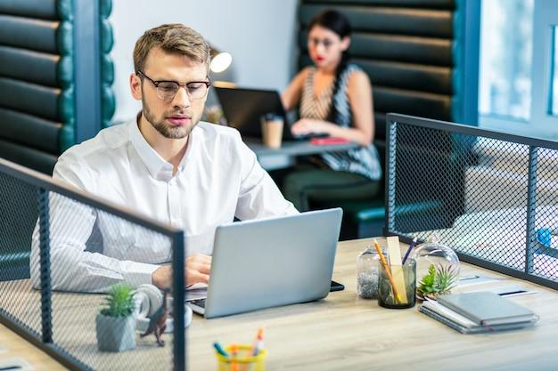 Надо подумать. сосредоточенный молодой мужчина сидит на своем рабочем месте и создает бизнес-план