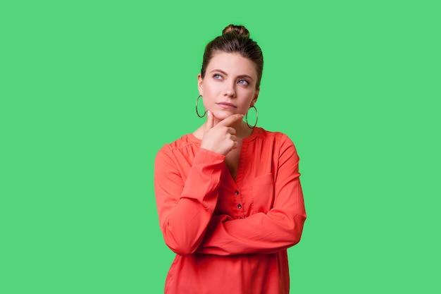 Надо подумать. портрет задумчивой элегантной молодой женщины с прической булочки, большими серьгами и в красной блузке, держащей ее подбородок и серьезно думающей. закрытый студийный выстрел изолирован на зеленом фоне