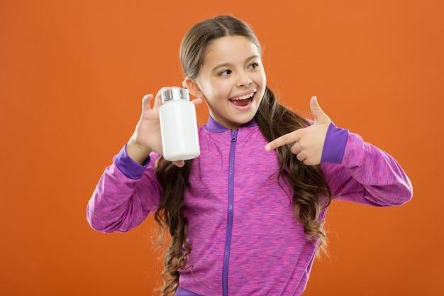 Нужны витаминные добавки. милая девочка ребенка принимает лекарства. лечение и медицина. натуральный продукт. детские поливитамины. принимайте витаминные добавки. девушка держит бутылку с лекарствами. концепция витамина.