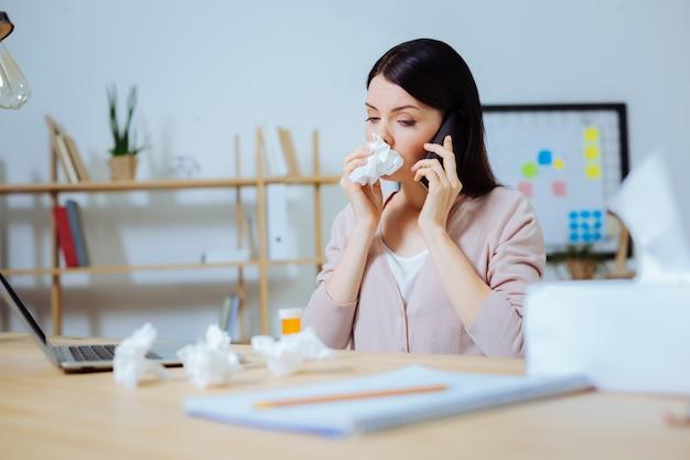 あなたの推薦が必要です。左耳の近くに電話を持って、仕事中に鼻水を持っているかなりブルネット