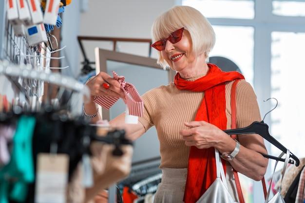 衣類の必要な部分。ファッショナブルな衣料品店に立っている間、ヘッドバンドを手に持っている赤いサングラスでポジティブな白髪の顧客の腰を上げる