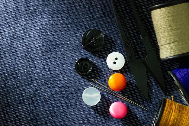 ジーンズの生地のプラスチック製のボタンと糸切りはさみに対して針と糸。上面図