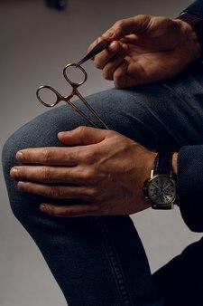持針器と外科用ナイフとビジネスウォッチのクローズアップ。
