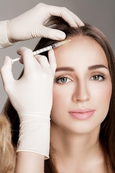 Needle mesotherapy. cosmetic been injected in woman's head. strengthen the hair and their growth