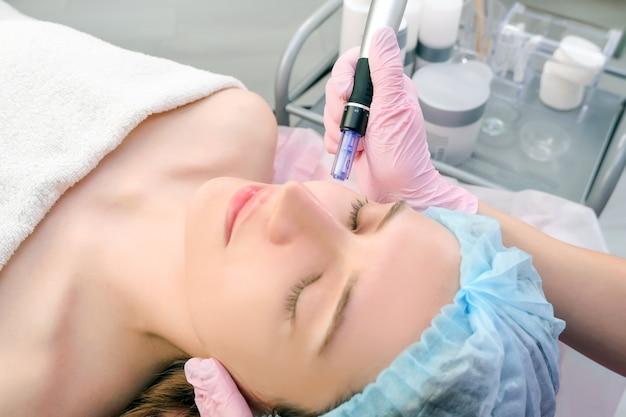 바늘 메조테라피. 미용사는 여자 얼굴에 바늘 메조테라피를 합니다. 미세침 회춘 치료를 받는 아름다운 여성. 바늘 들기