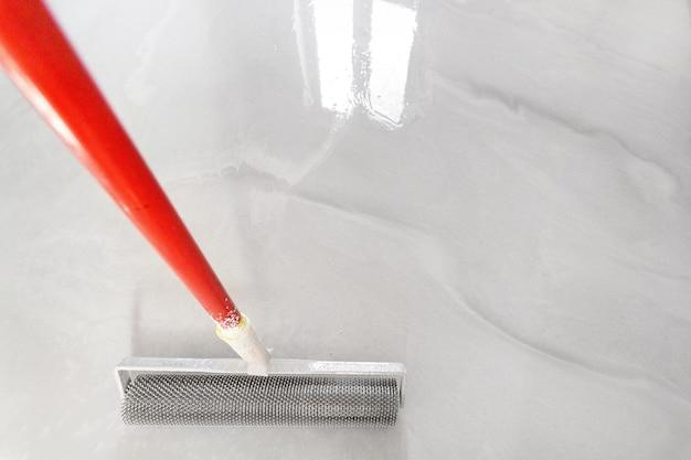 셀프 레벨링 바닥용 니들 롤러 도구. 액체 바닥 표면에 공간을 복사합니다.
