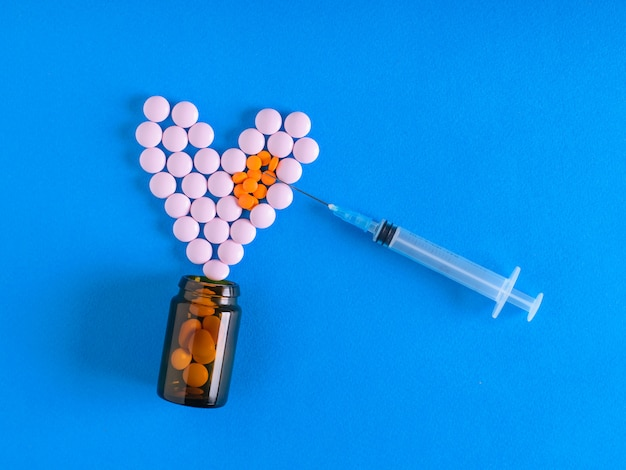 The needle of the syringe is aimed at the heart of the pills on a blue background. the view from the top. the concept of treatment and prevention of diseases. flat lay.