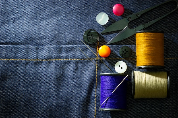 Needle and threads against plastic button and thread cutting scissors on jeans fabric.