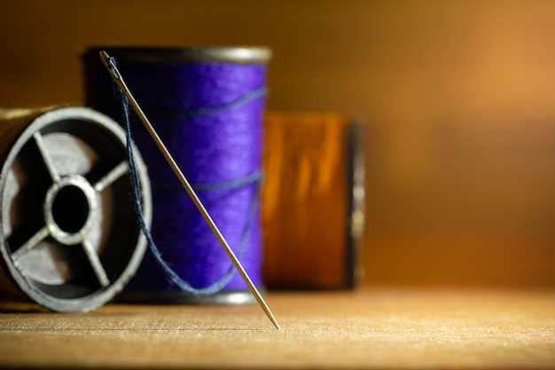 Needle and threads on wooden table.