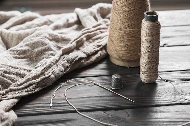 Needle; tread spool and thimble with jute fabric on wooden table