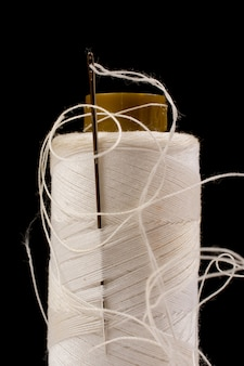 Needle and white cotton, tangled yarn on roll for sewing. thread used in fabric and textile industry. black background