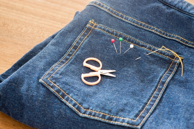 Needle with a thread through the jean