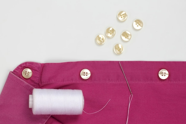 Needle with white threads and sewn pearl buttons on the shirt