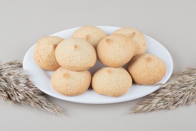 Стебли иглы рядом с тарелкой печенья на мраморном фоне.