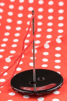 Needles in black button with pattern background