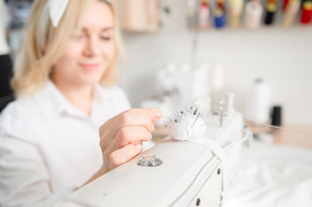 Needles in a pillow on a sewing machine workplace of a seamstress sewing concept dressmaker work