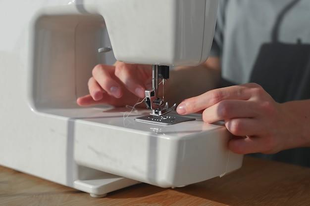 ミシンクローズアップの針穴から糸を挿入する針女の手作業開始