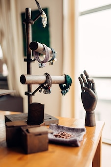 Needlework accessories, bracelets and wooden hand in workshop. handicraft tools. handmade fashion jewelry
