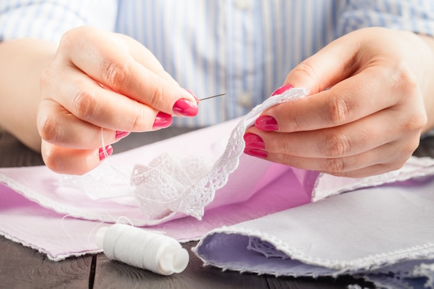 Needlework, sewing and tailoring concept - tailor woman with thread in needle stitching fabric. hands sewing with a needle and thread. fingers pulling thread into the needle