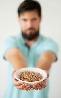 Needy man holding bowl of food