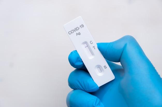 ゴム手袋をはめた医師の手で病気を迅速に検出するためのネガティブコビッド抗原検査