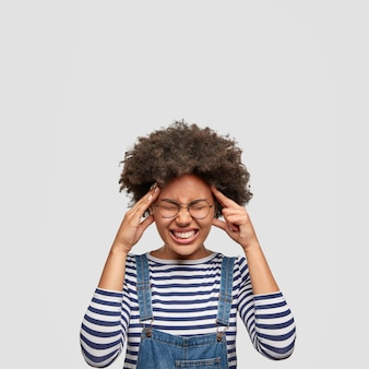 Понятие отрицательных эмоций и чувств. недовольная афроамериканка держит руки на висках, небрежно одетая, позирует у белой стены. у темнокожей женщины болит голова после работы