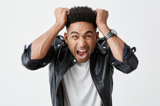 Negative emotions. close up portrait of young beautiful black-skinned man with afro hairstyle in white t-shirt and leather jacket ripping out hair with hands, screaming loudly with mad expression.