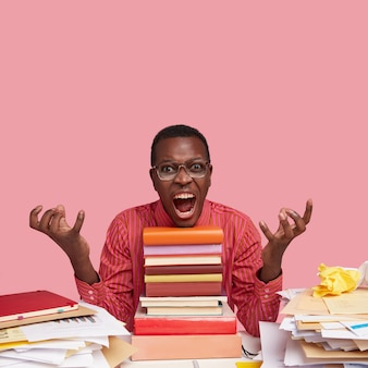 Negative emotions concept. dissatisfied furious young man with dark skin, gestures with anger, opens mouth widely, sits in front of books