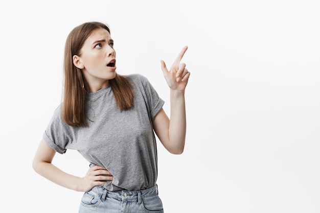 Negative emotions. portrait of expressive young good-looking student girl with dark hair in grey clothes looking aside with opened mouth and mean expression, pointing on white wall with finger. copy