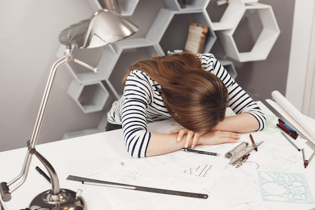 Negative emotions. portrait of young fashionable female freelance architect lying on hands at table, being tired after working too much, dreaming of sleep